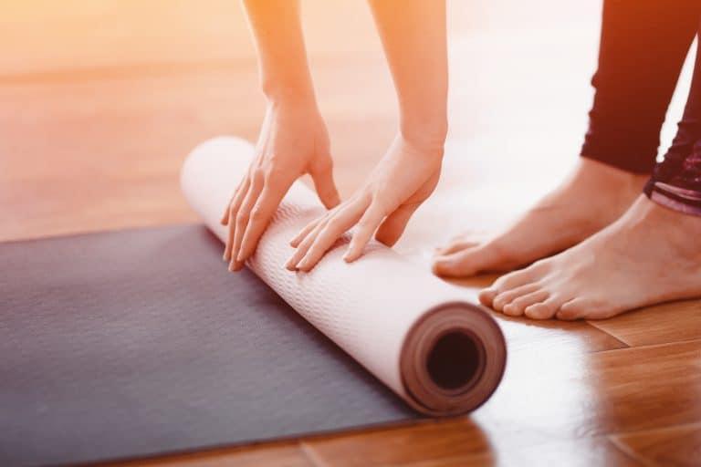 Detailaufnahme Frau rollt Yogamatte auf