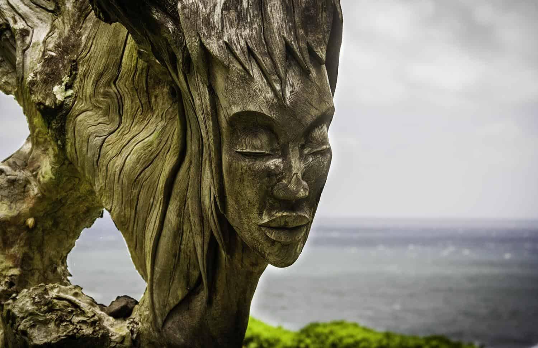 Detailaufnahme Holzskulptur einer Frau vor Ozean auf Maui, Hawaii