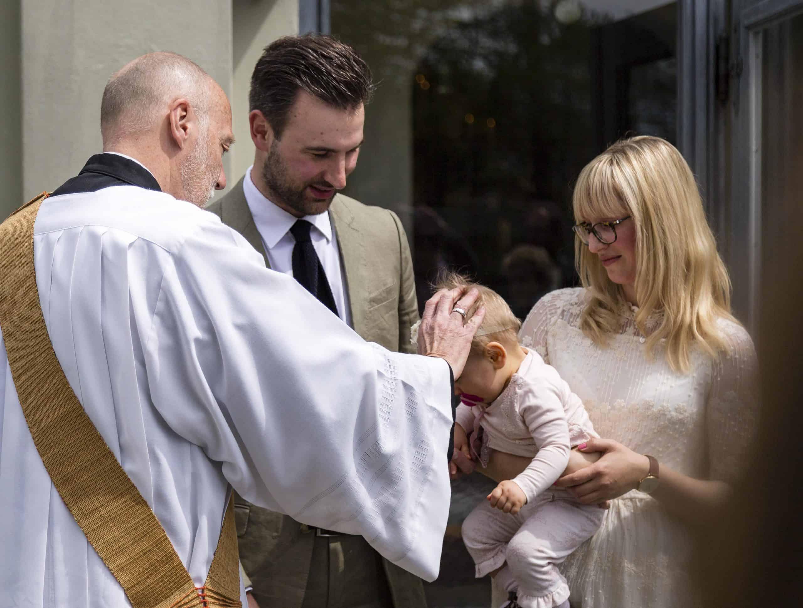 Fotografie Taufe Baby auf Arm der Mutter, Pfarrer legt Hand auf den Kopf auf
